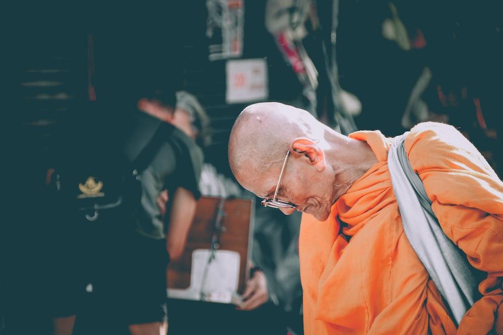 monk in orange dress looking down