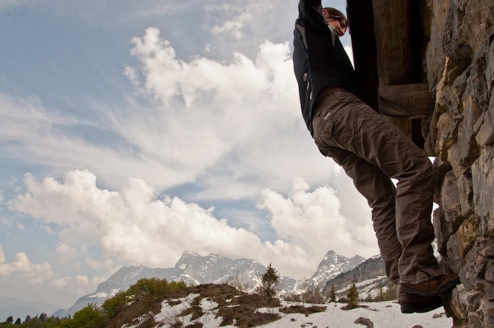 man climbing on wall during daytime
