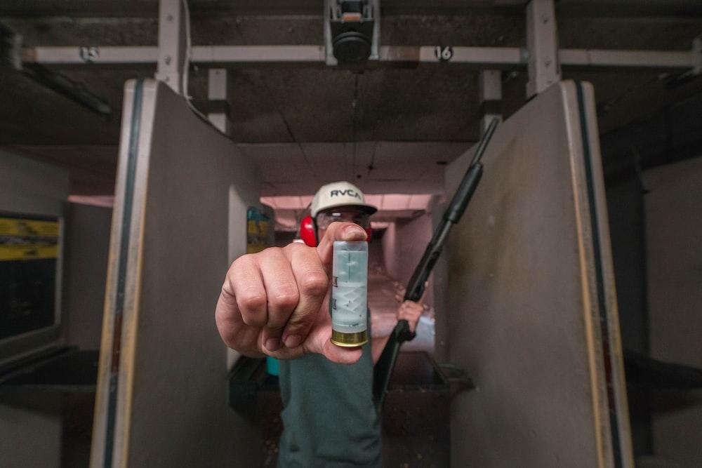 person holding shotgun bullet