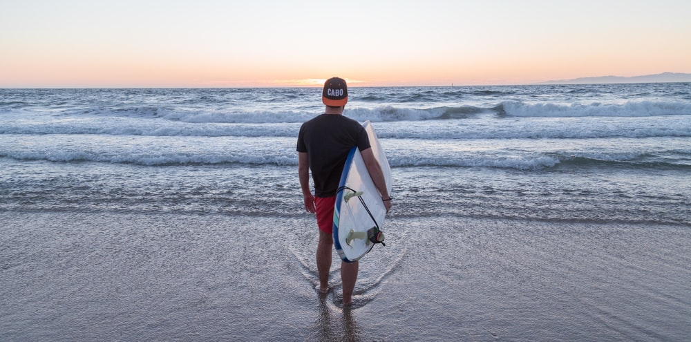 person standing while carrying surfboard facing sea