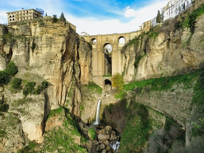 waterfalls blow concrete bridge and buildings at daytime spain zoom background