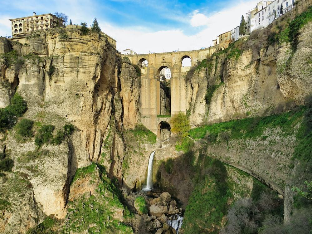 waterfalls blow concrete bridge and buildings at daytime