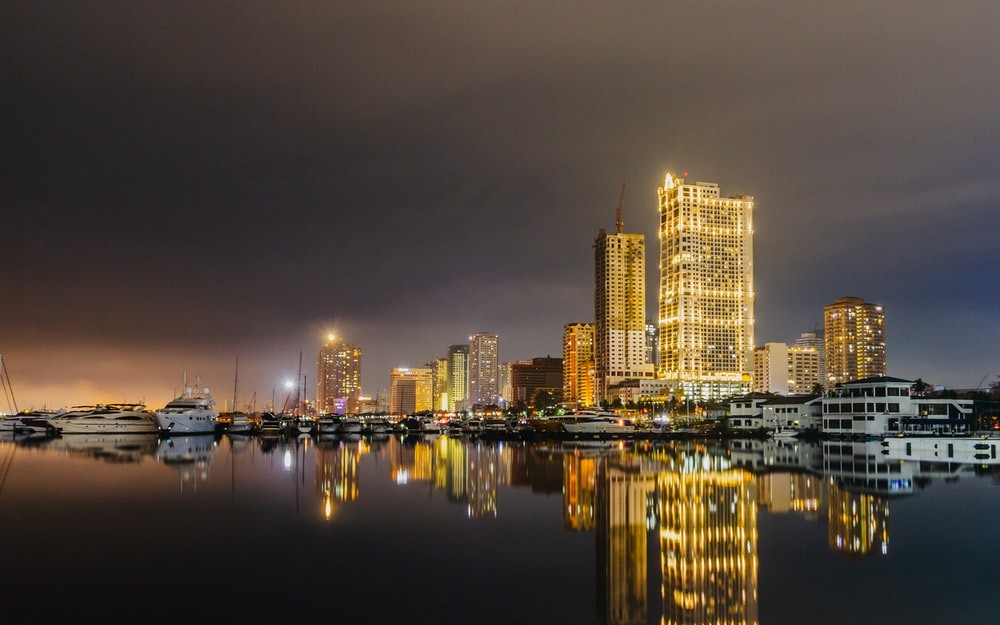yellow lighted buildings by the harbor under grey cloudy sky