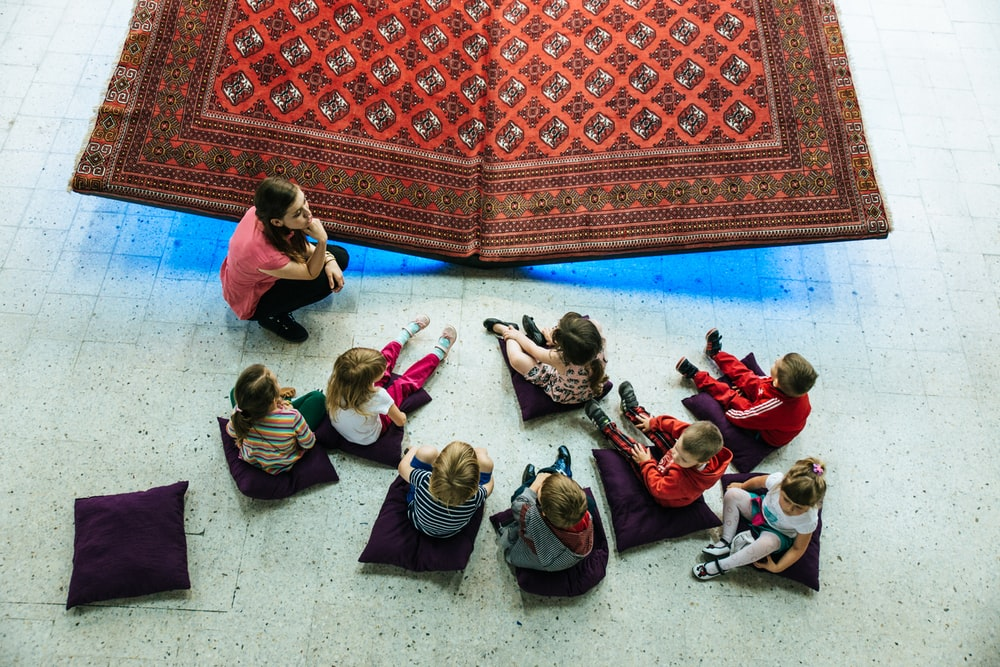 children and woman sitting on floor with pillows