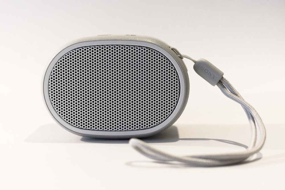 oval grey portable speaker on white surface