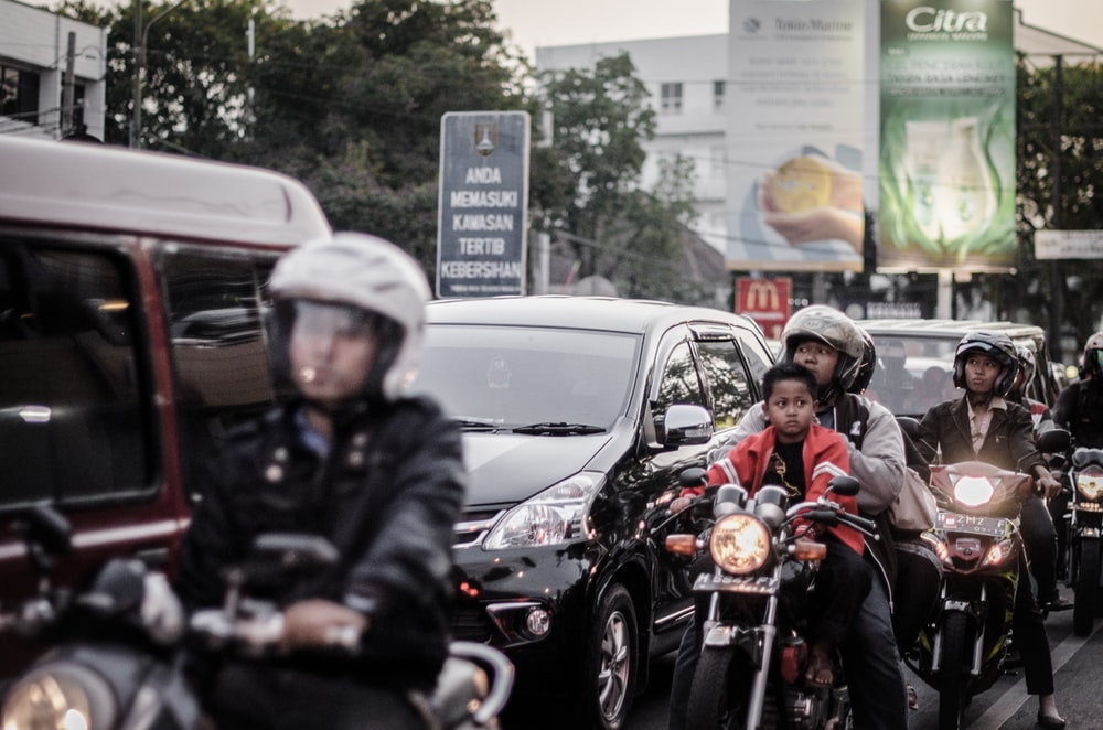 people riding motorcycles beside vehicles during daytime