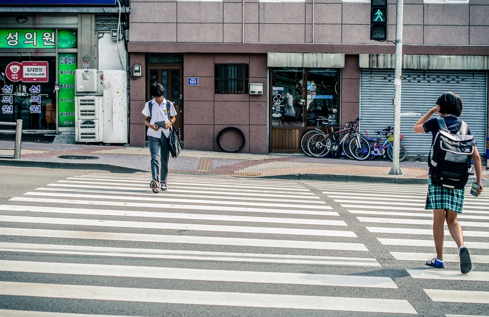 man and woman crossing in pedestrian lane during daytime