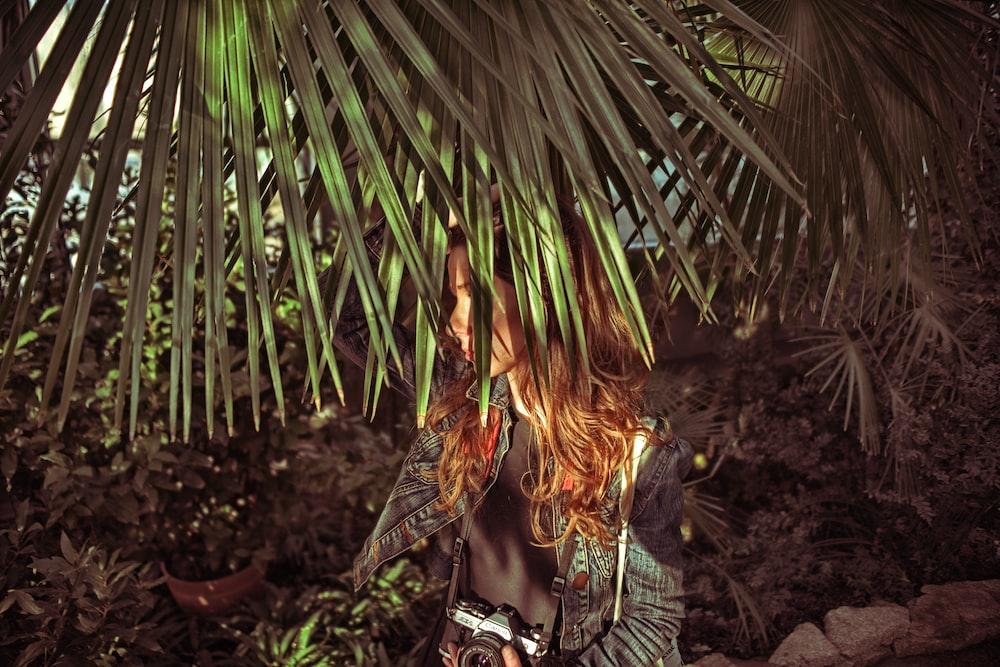 standing woman beside fan palm