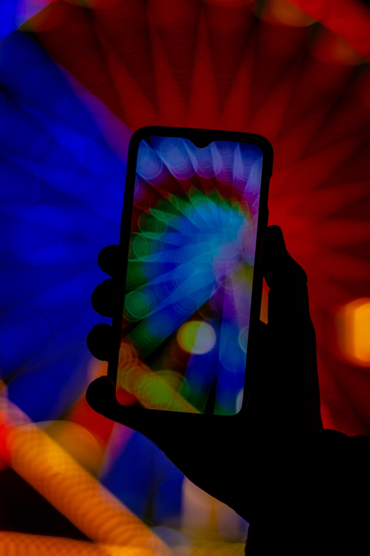 black smartphone displaying multicolored wallpaper