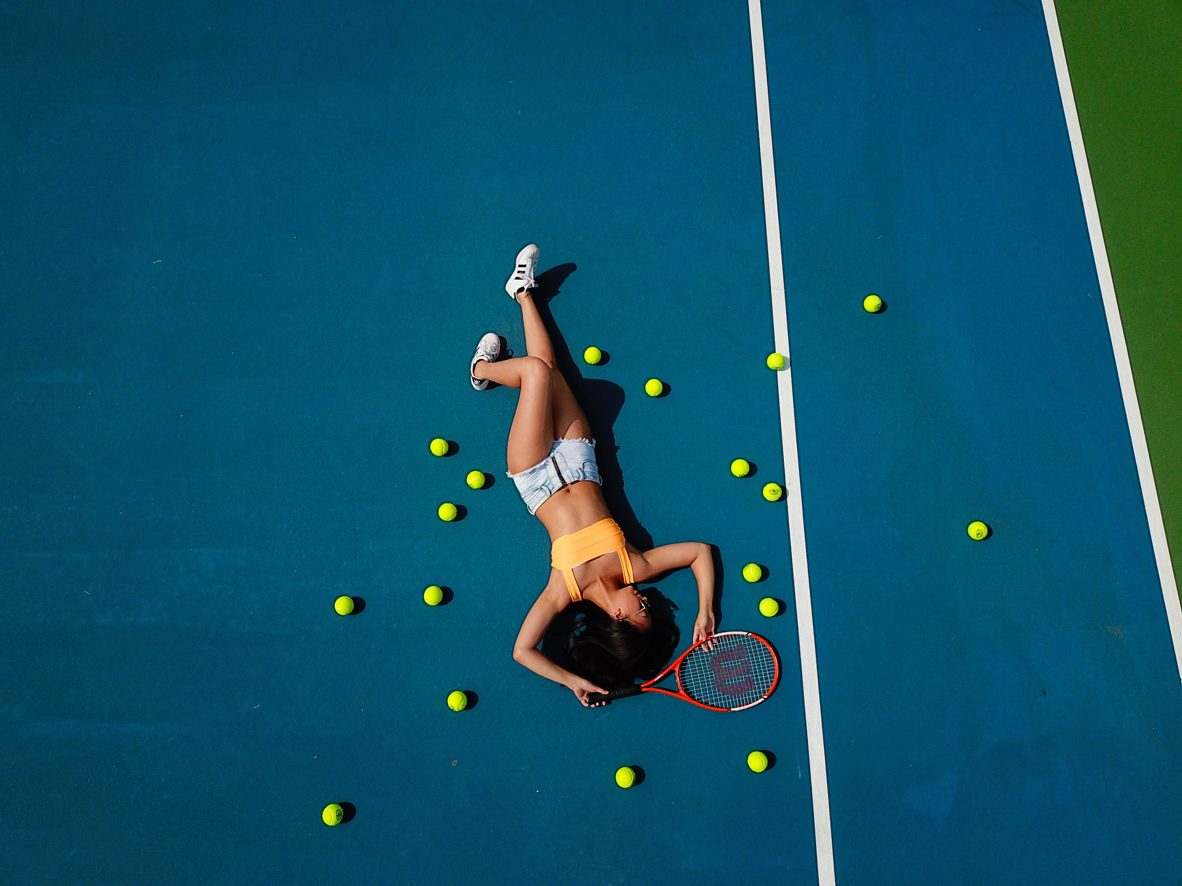 woman in yellow crop top laying down on hard court