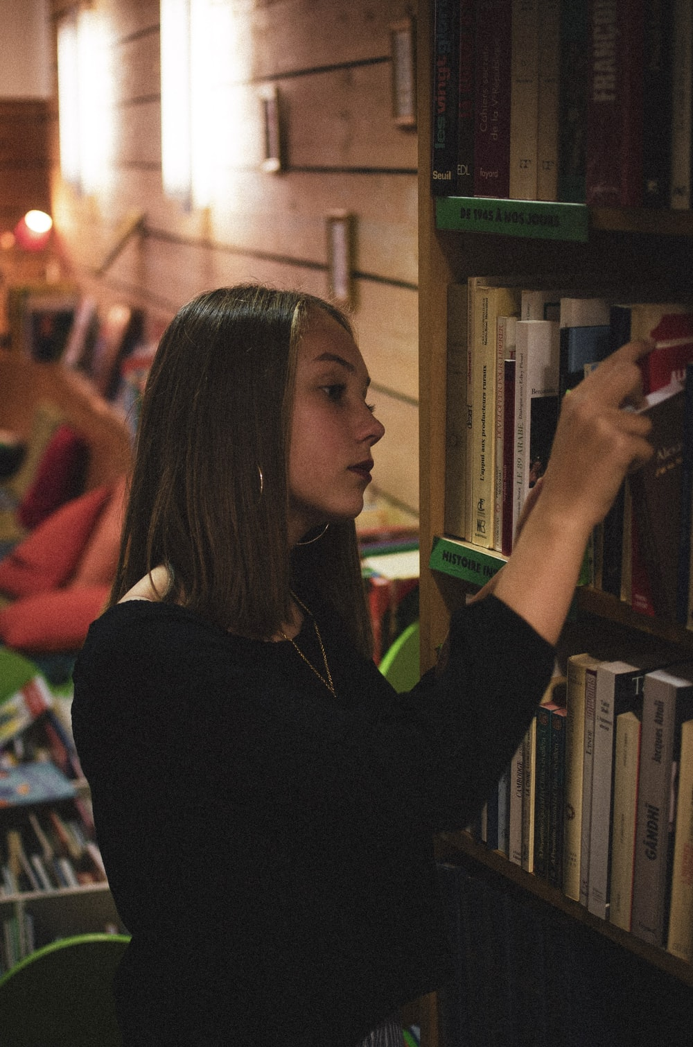 woman getting books from shelf