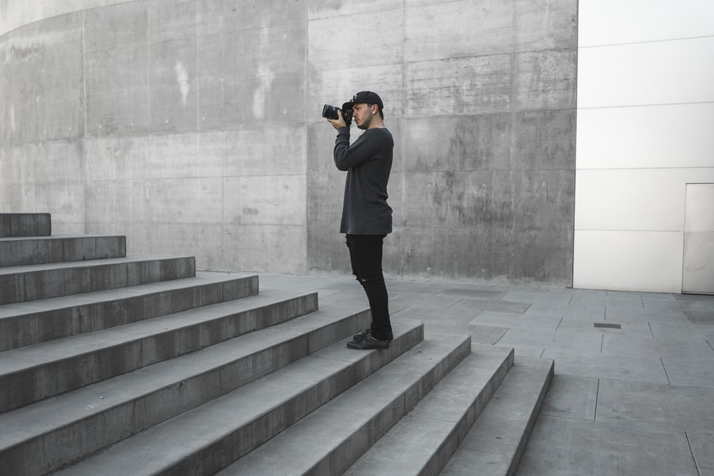 man taking picture of gray stairs