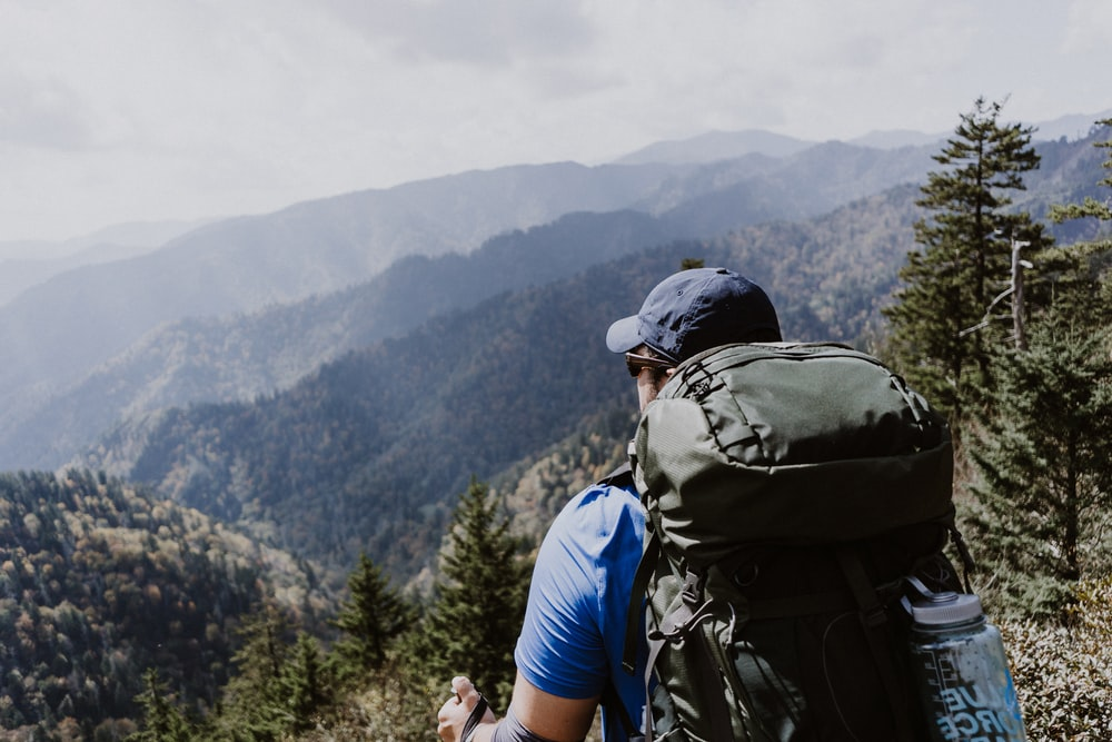 man standing on top of mountain with backpack