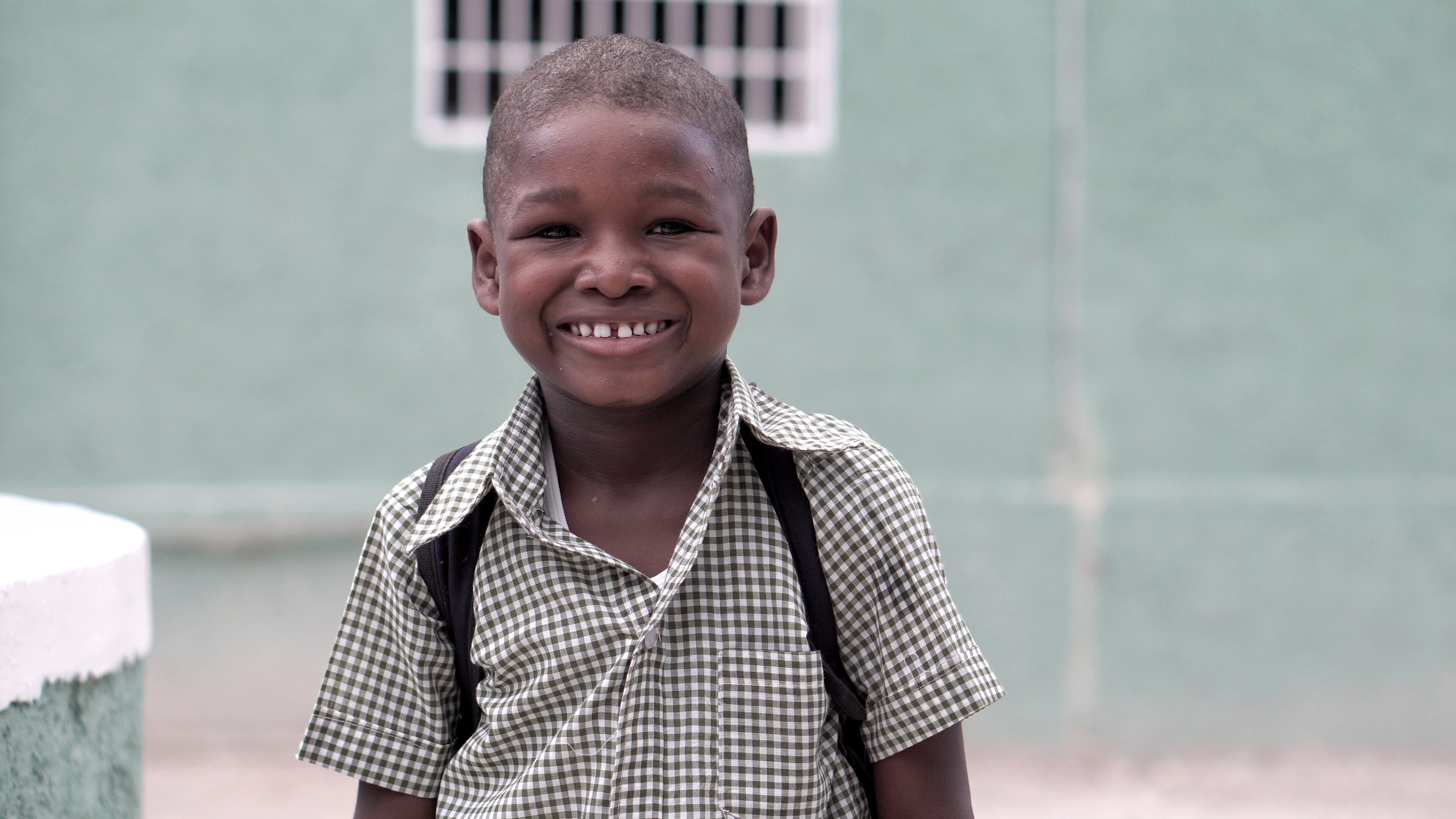 boy smiling carrying backpack