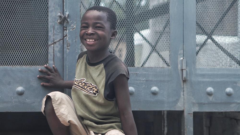 smiling boy sitting beside gray metal board