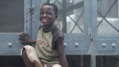 smiling boy sitting beside gray metal board haiti zoom background