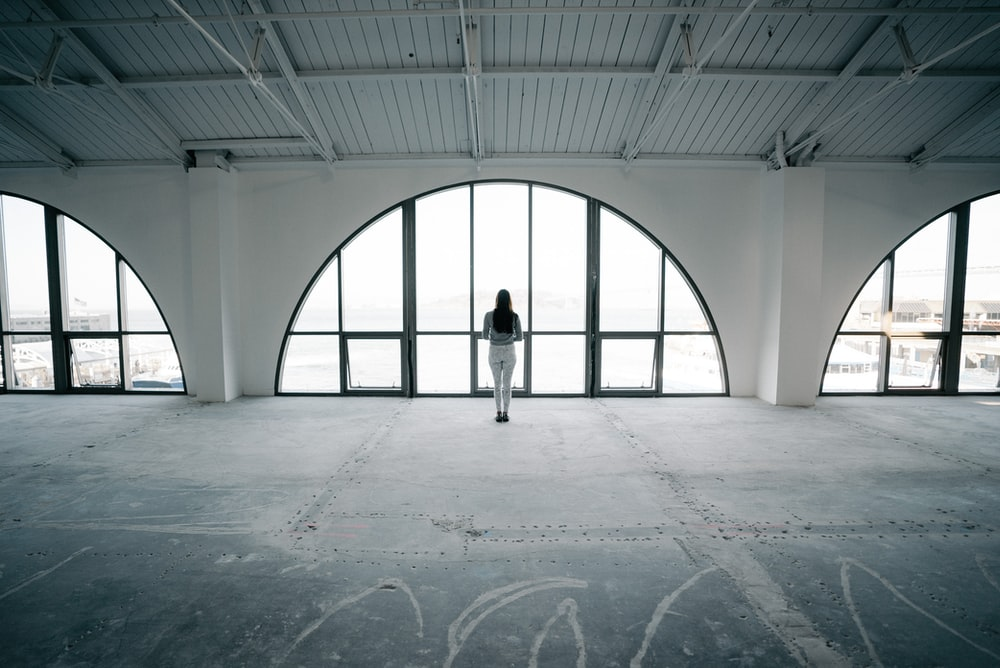 landscape photography of woman standing in front of glass window