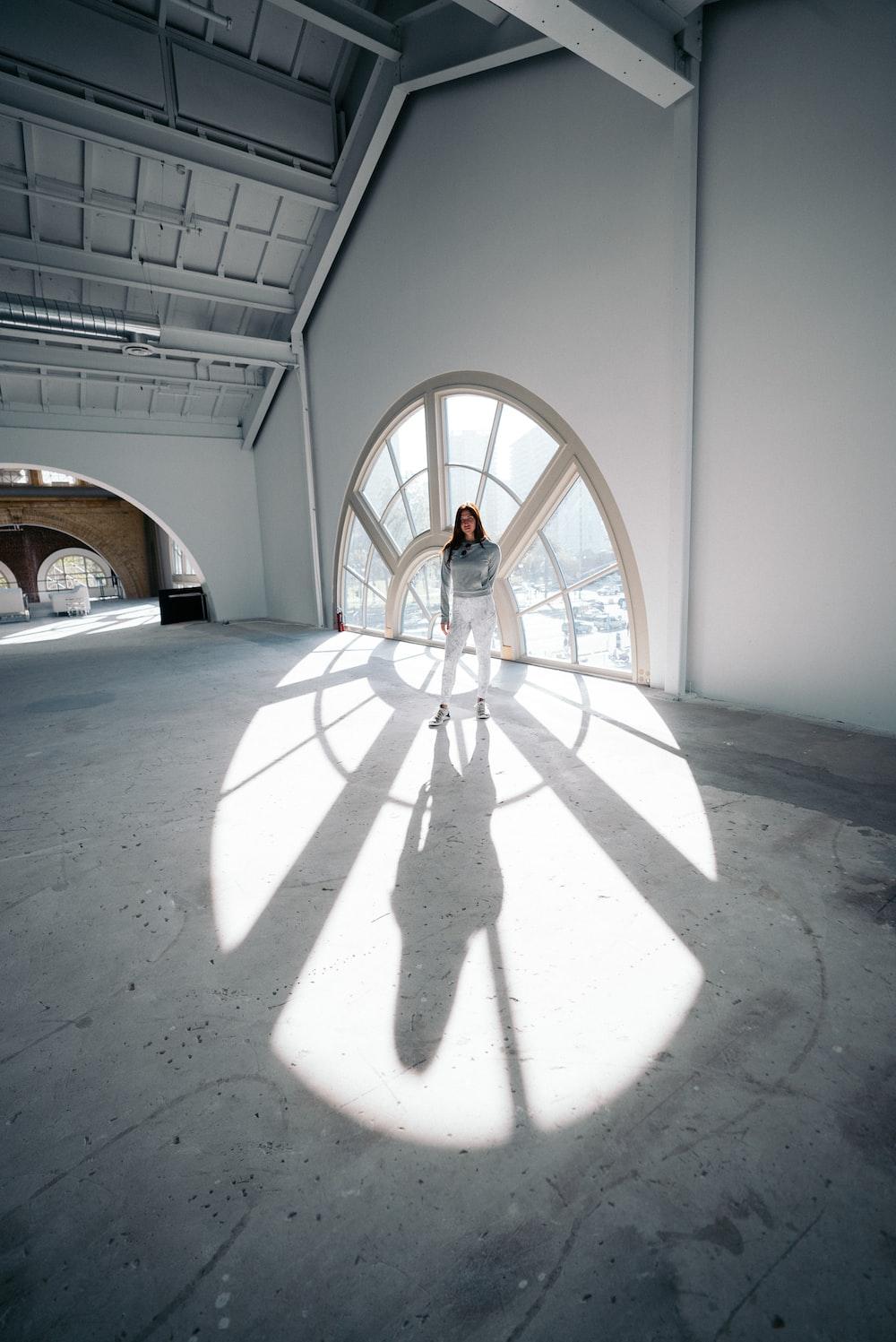 woman standing near glass window of an empty building