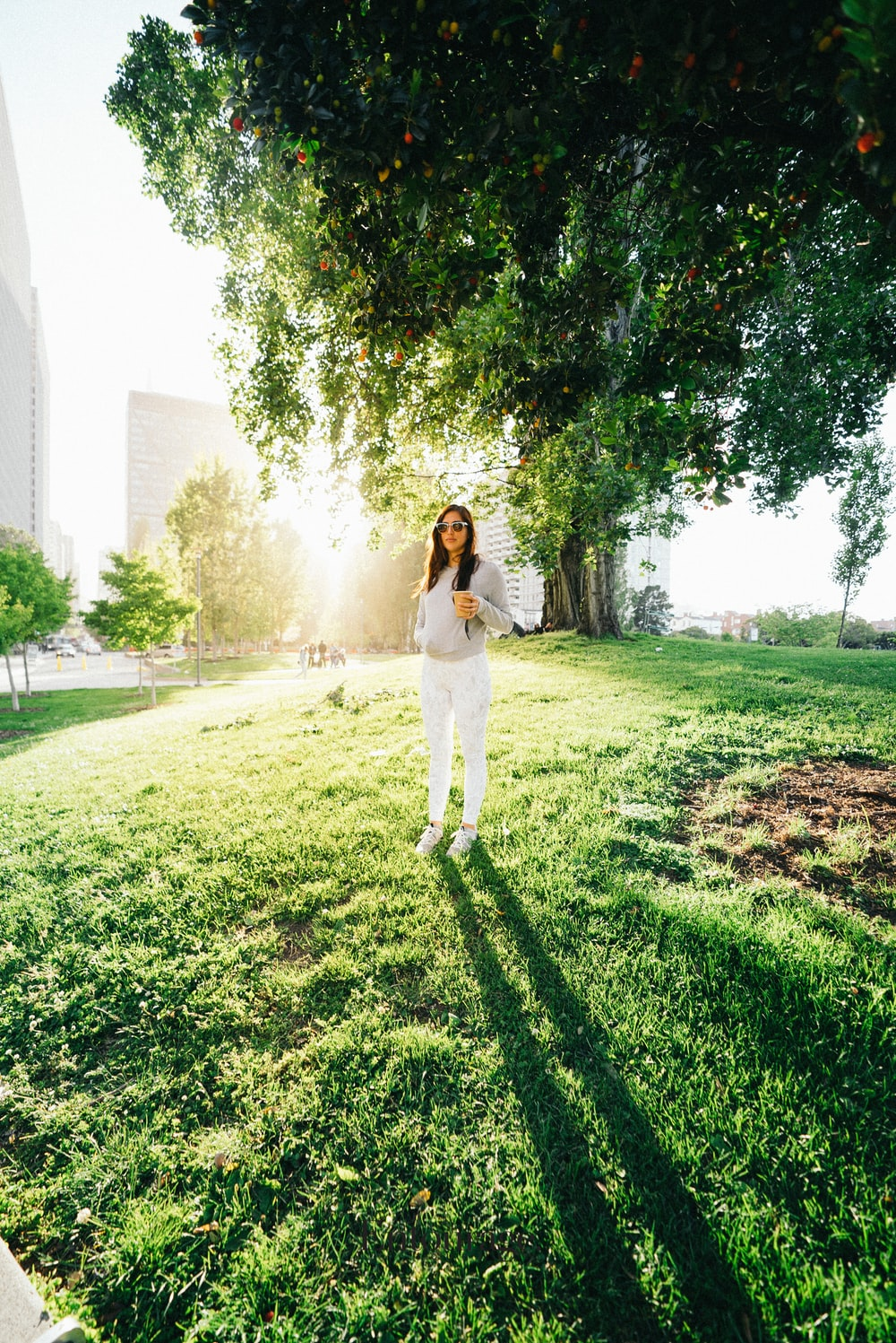 woman in white pants and grey sweater stands under green tree