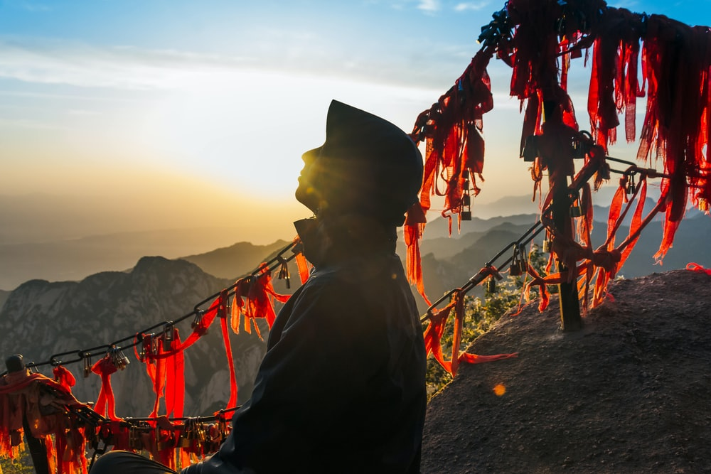 silhouette of man standing on cliff of mountain during sunset