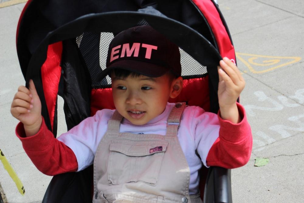 boy wearing black cap riding stroller