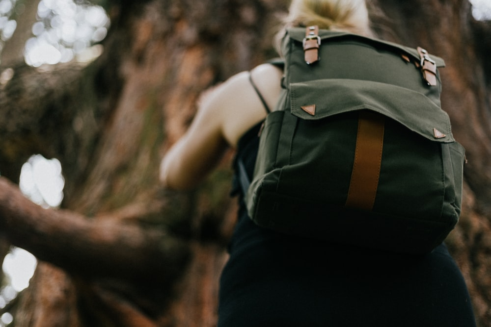 girl wearing green backpack climbing tree