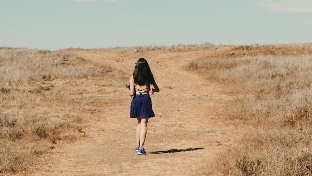 woman in blue dress walks on dirt road