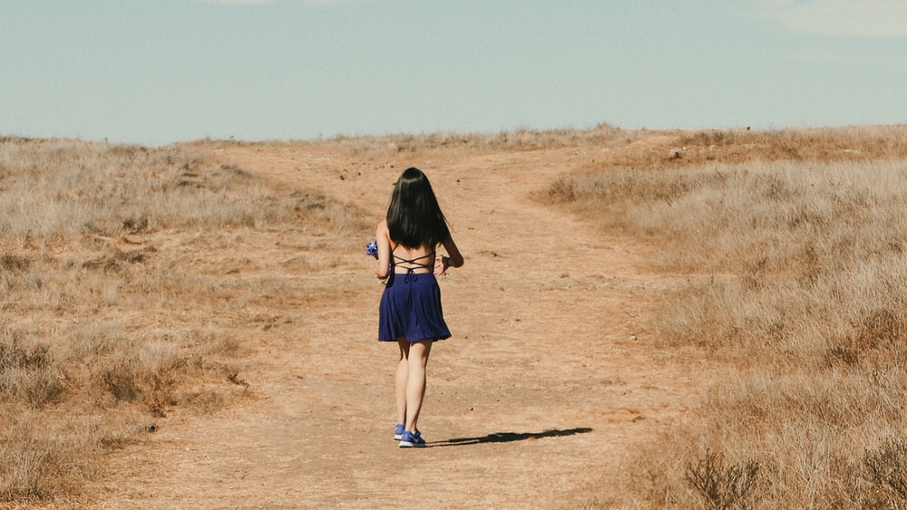 woman in blue dress walks on dirt road
