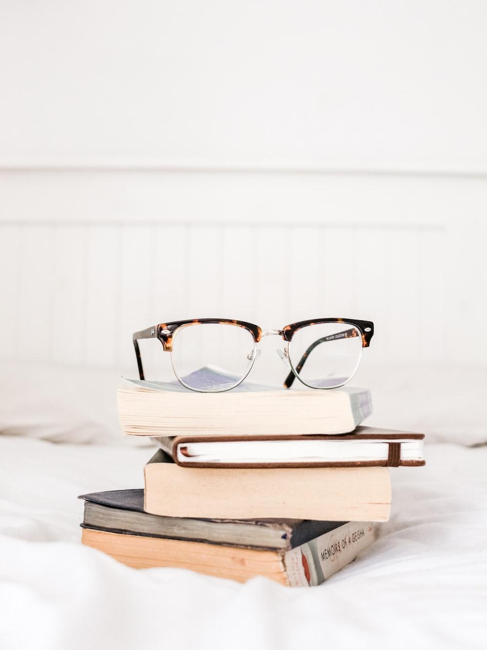 eyeglasses on pile books