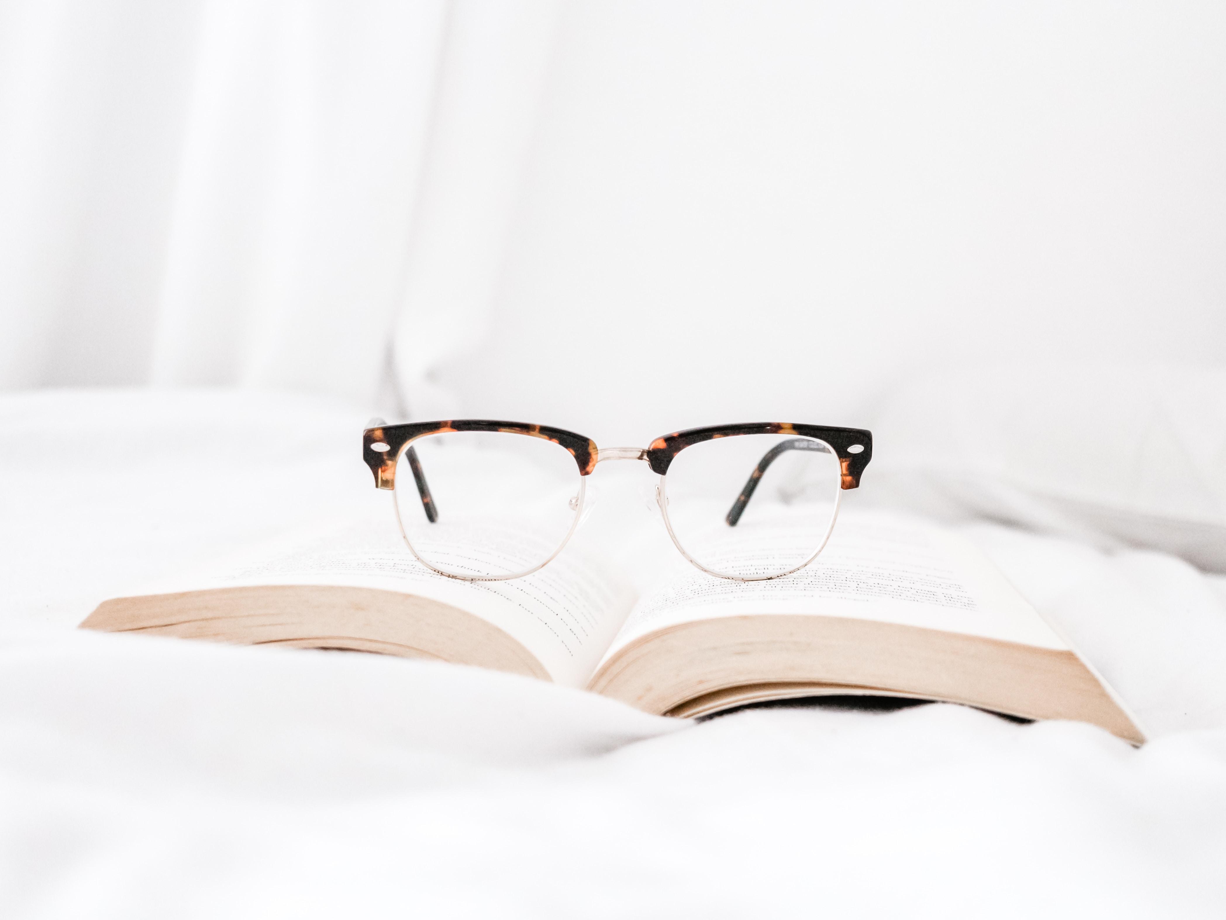 eyeglasses with tortoiseshell cat frames on book