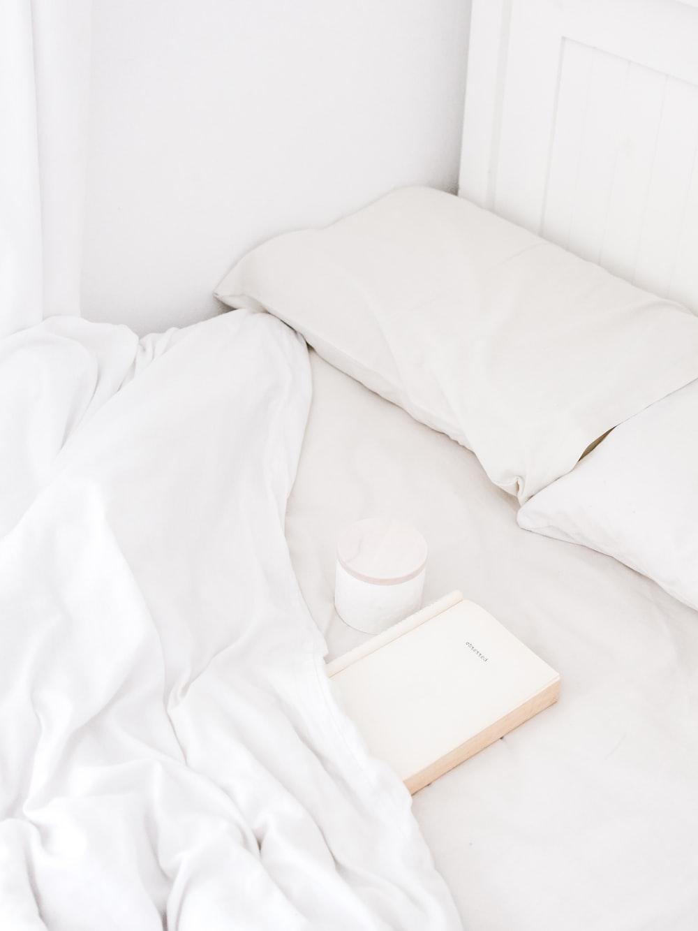white portable speaker on bed