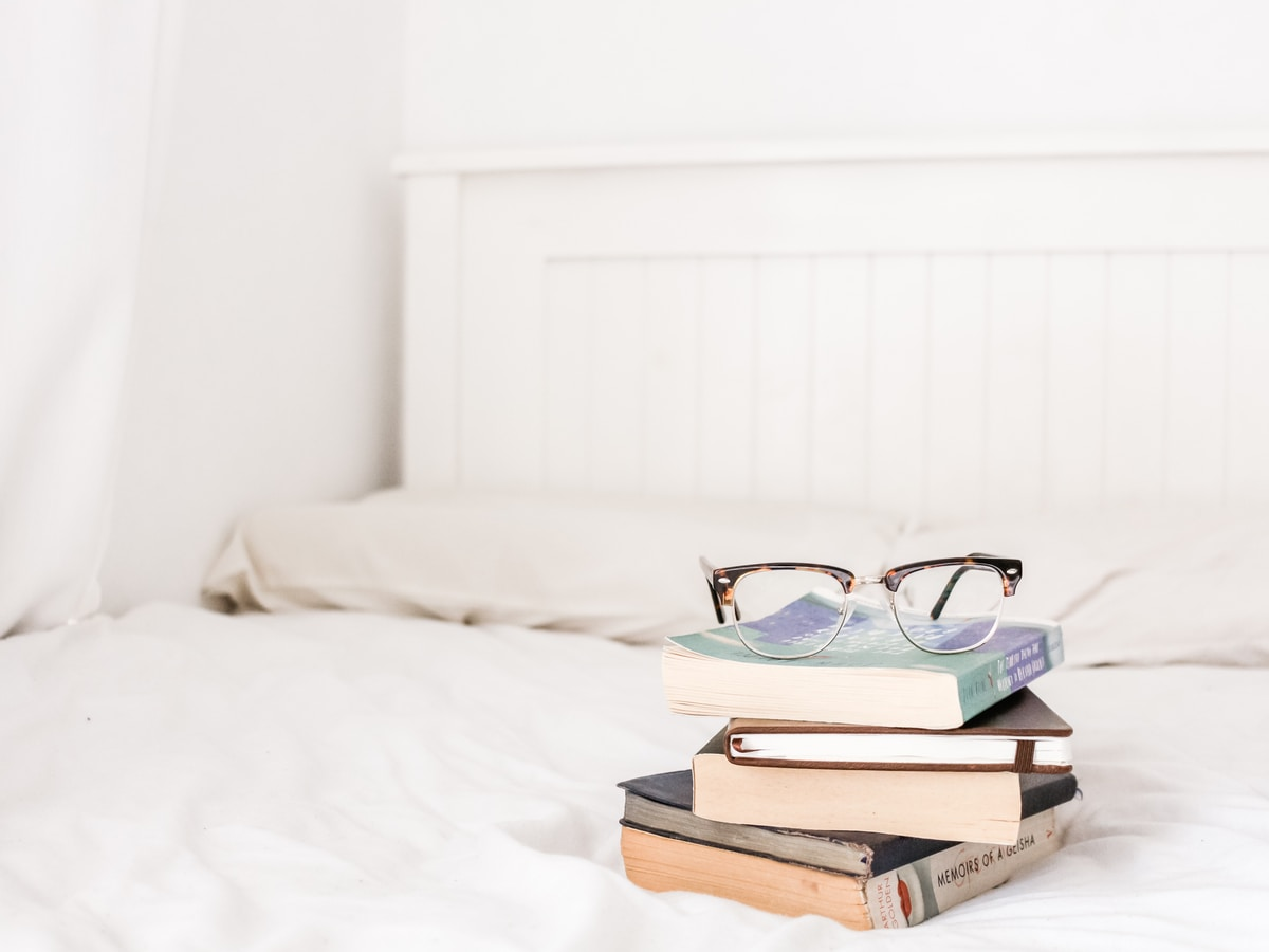 eyeglasses on top of a stack of books on a bed