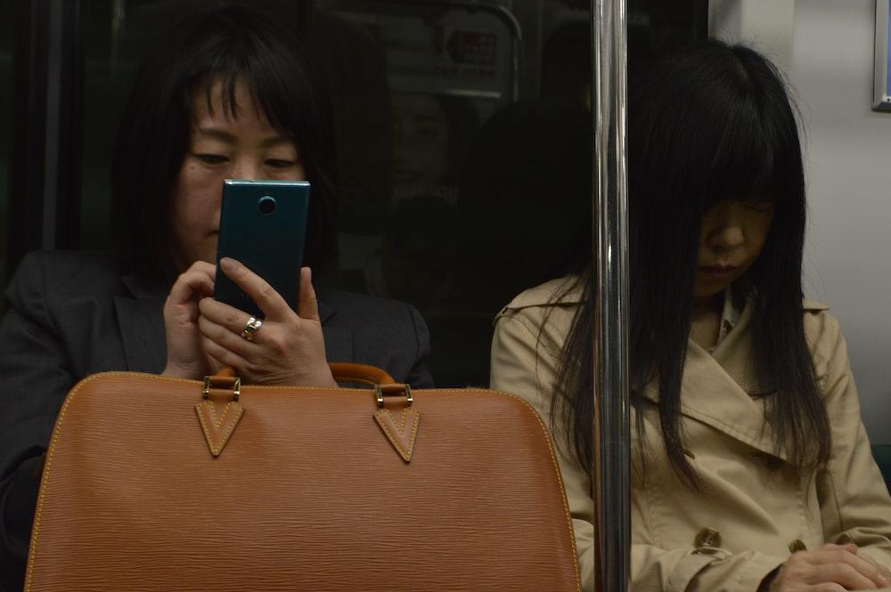 woman in train sits beside woman in beige coat