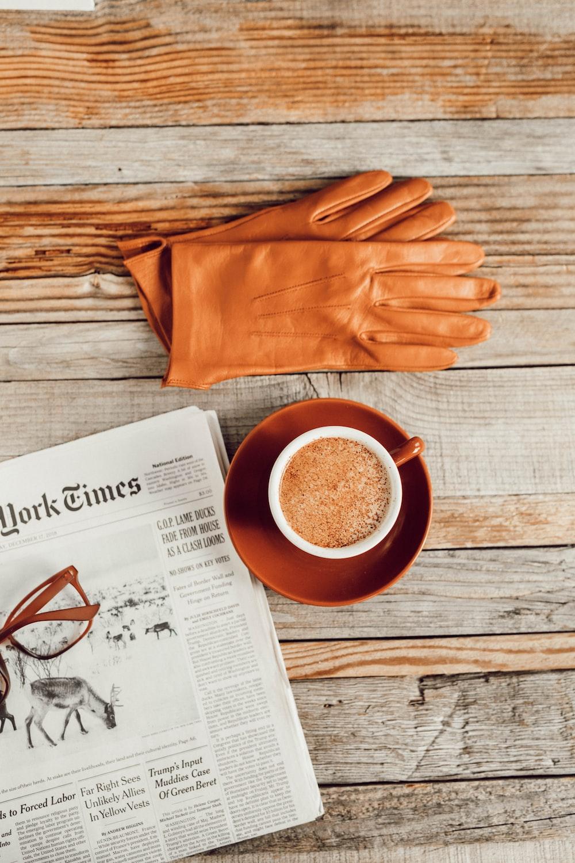 brown leather gloves near mug