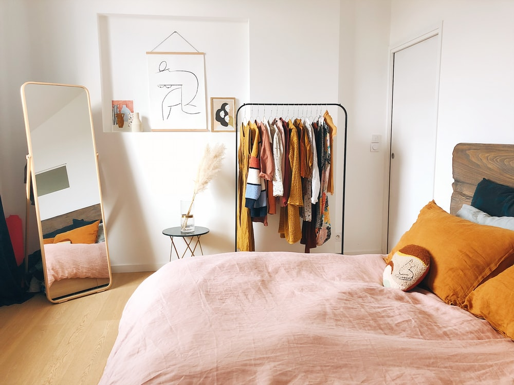 hanging clothes on rack near bed and door