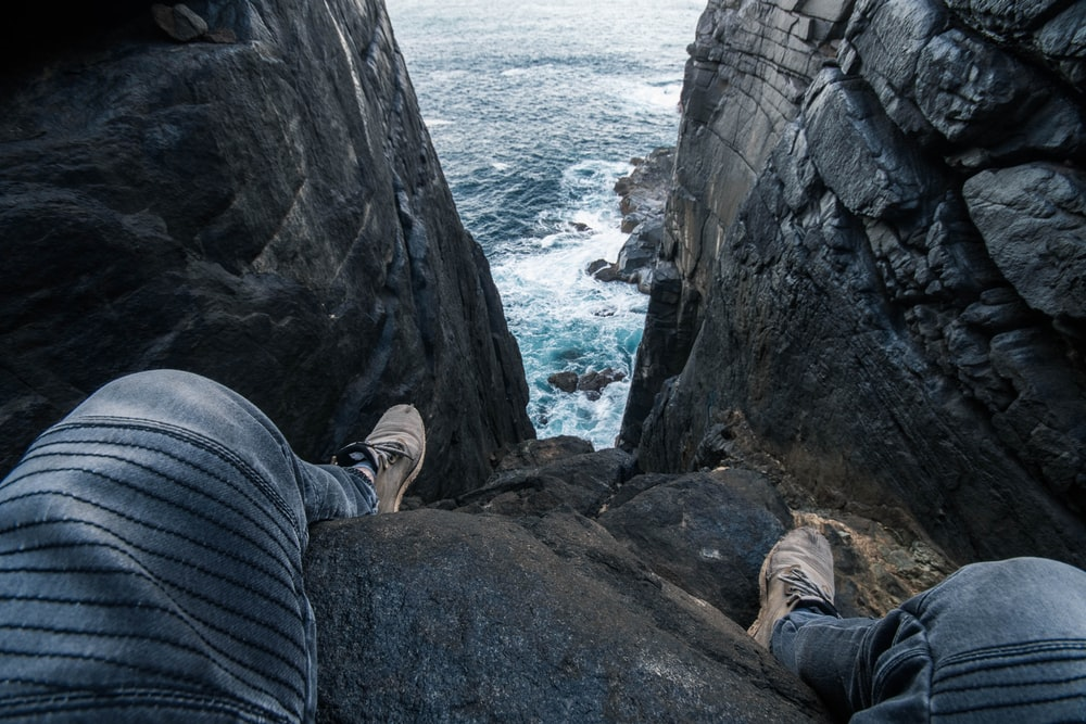 person wearing gray jeans standing on sea cliff during daytime