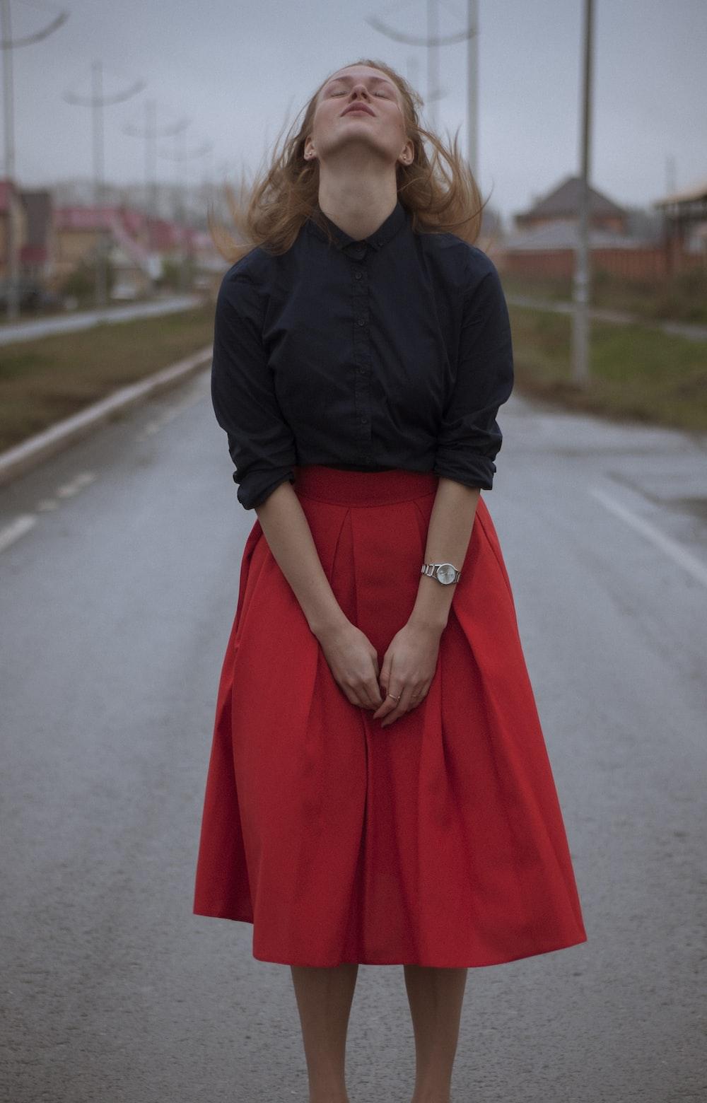 woman wearing black dress shirt and red long skirt