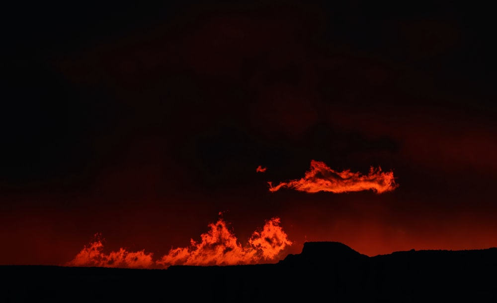 crimson clouds over silhouette of hills