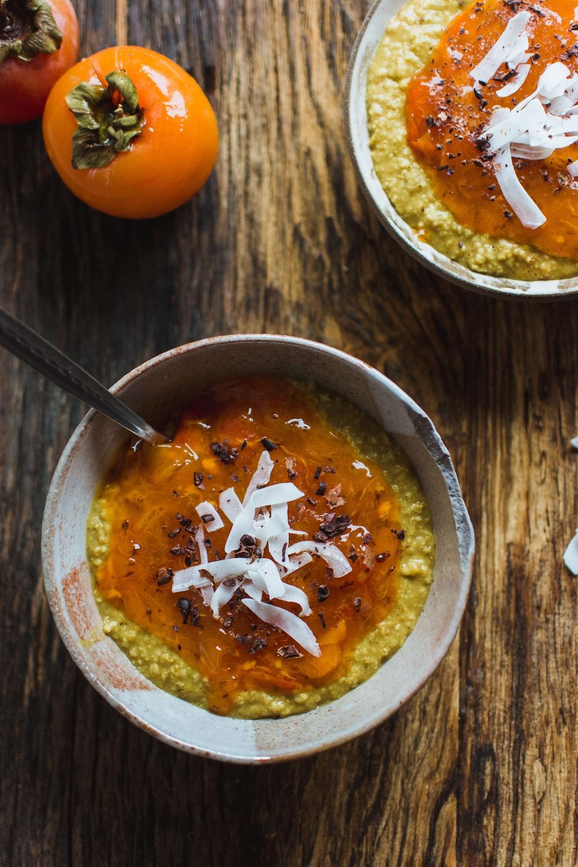 porridge on bowl beside persimmon