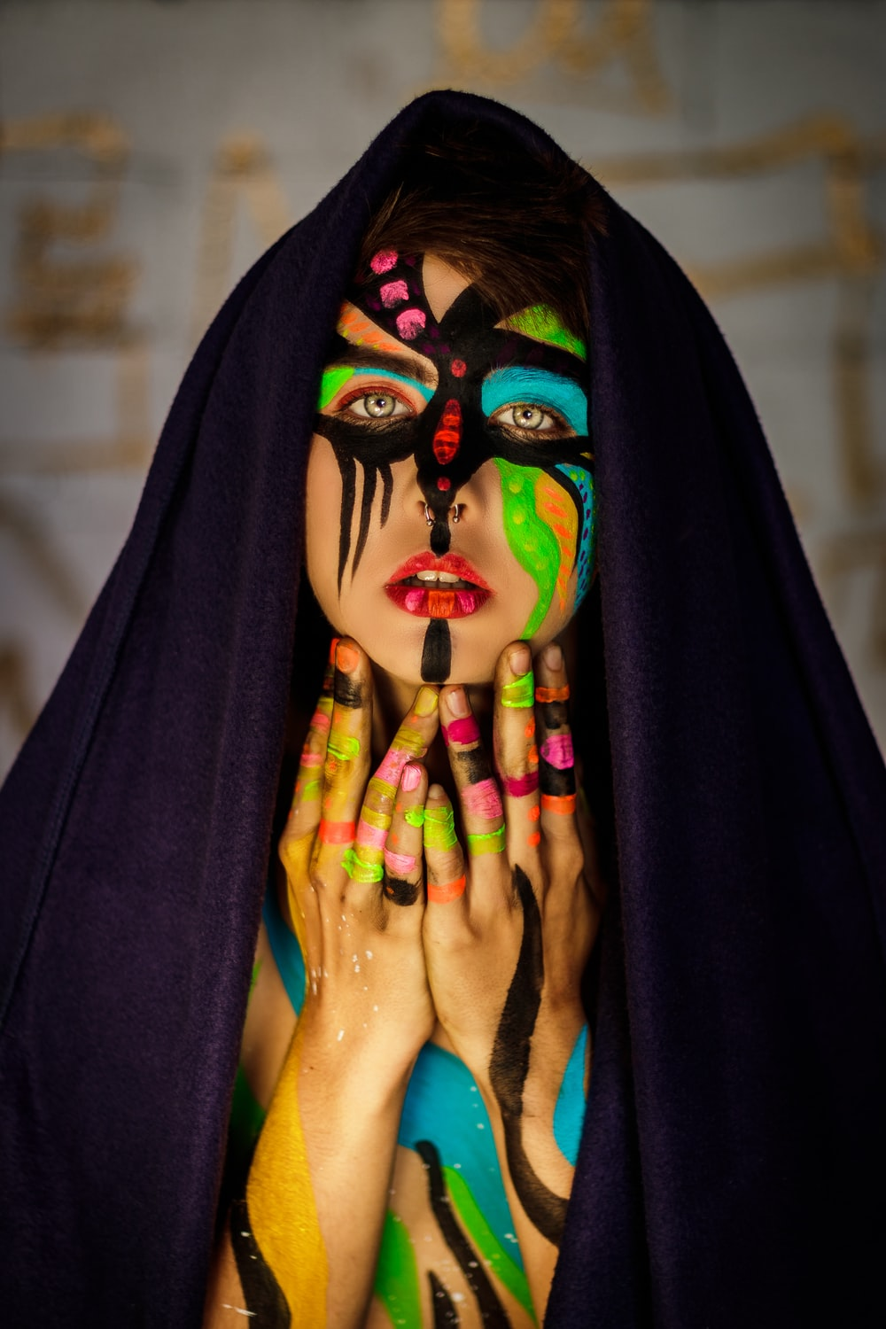 woman in black cloak with multicolored facial and body paint
