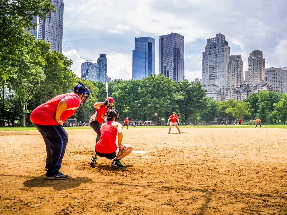 group of people playing baseball at daytime