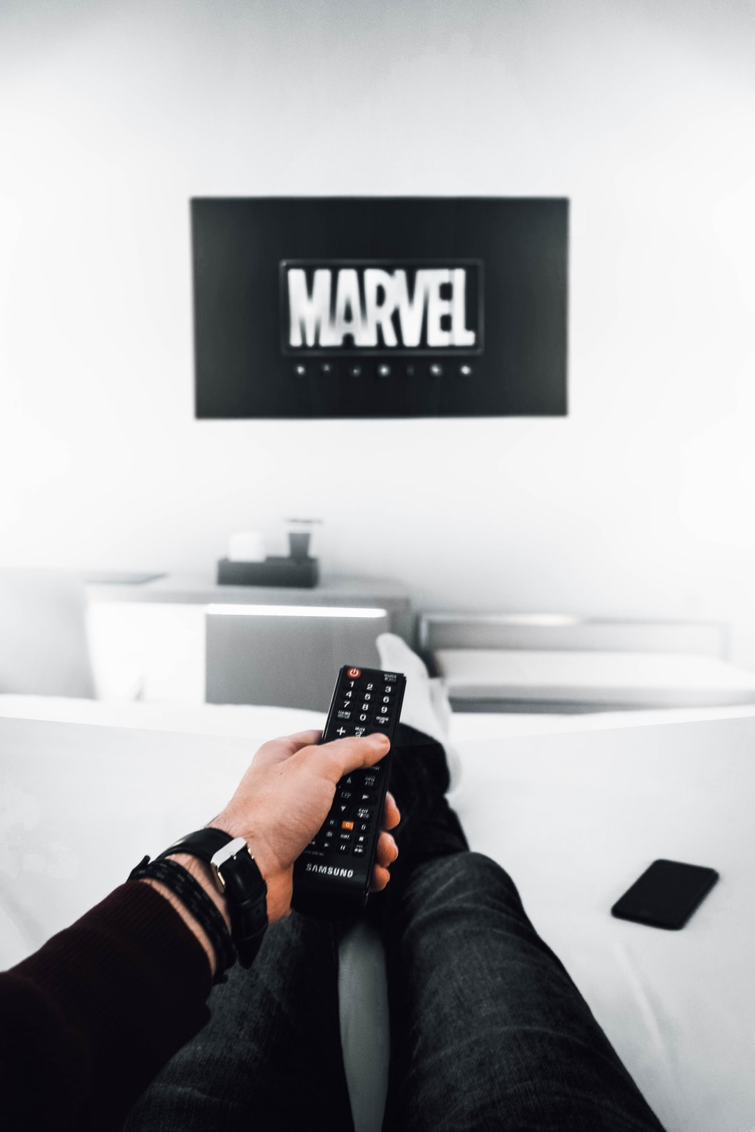 man holding remote control with Marvel logo on TV