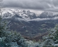 snow covered mountain range across green valley