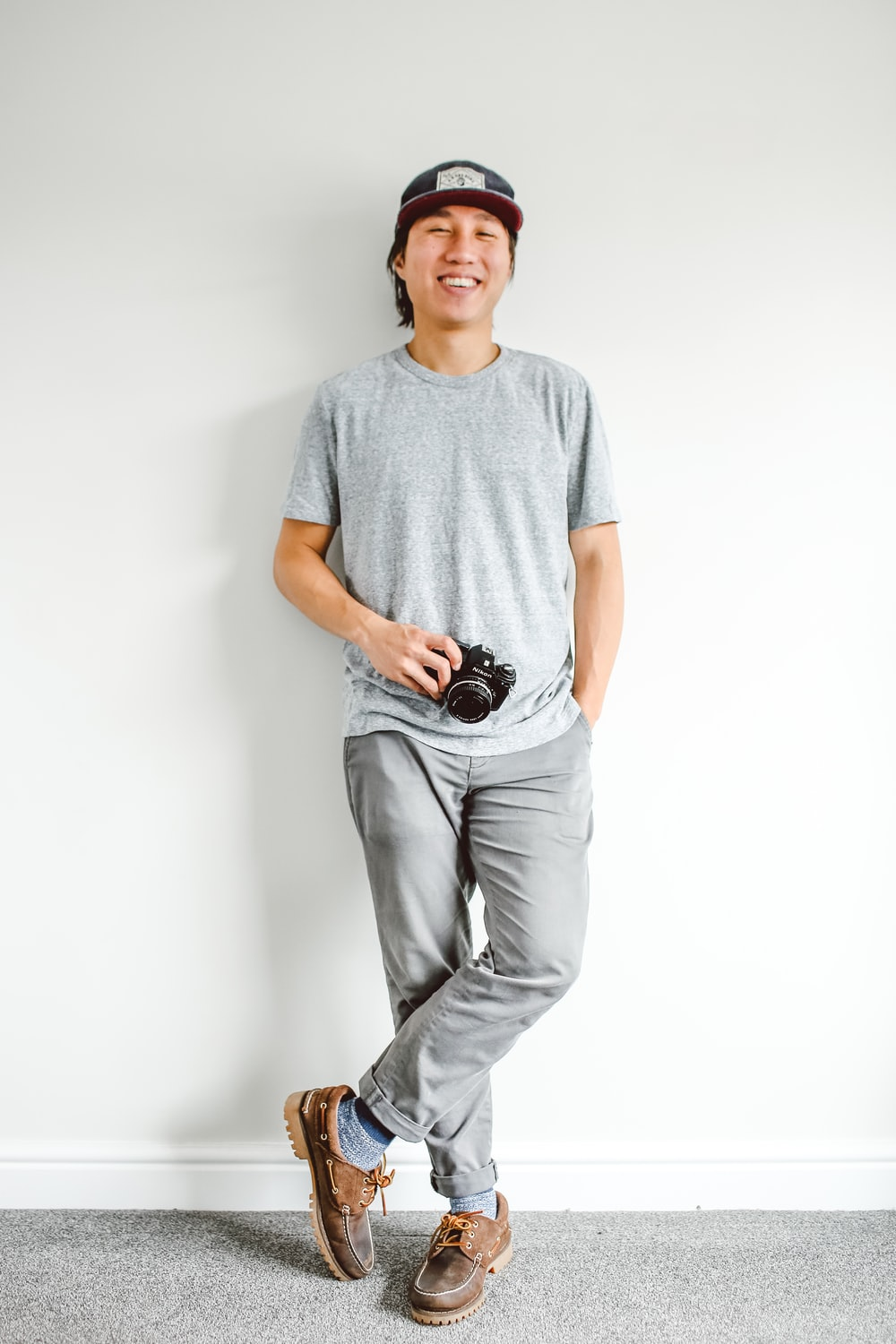 man standing and leaning by wall while holding camera