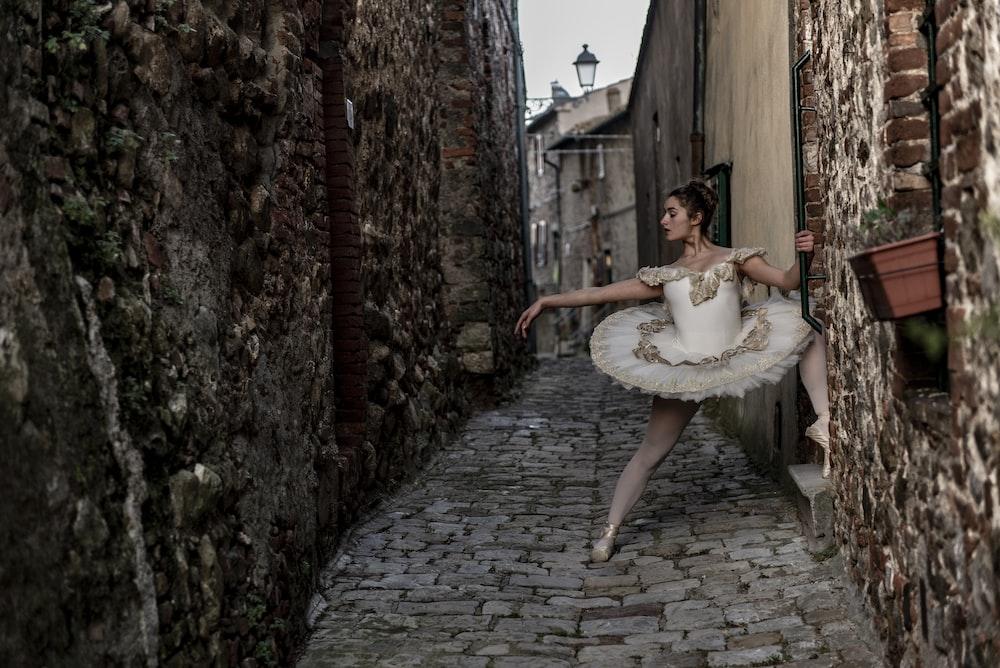 ballerina standing between two brown walls
