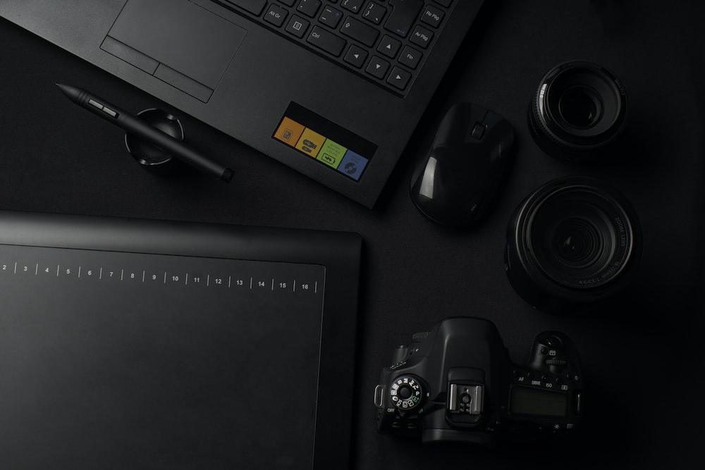 black DSLR camera besides computer mouse