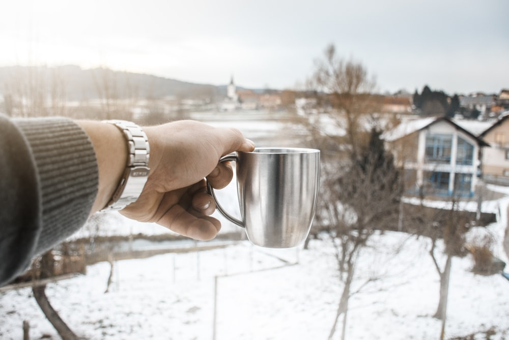 person holding silver metal mug