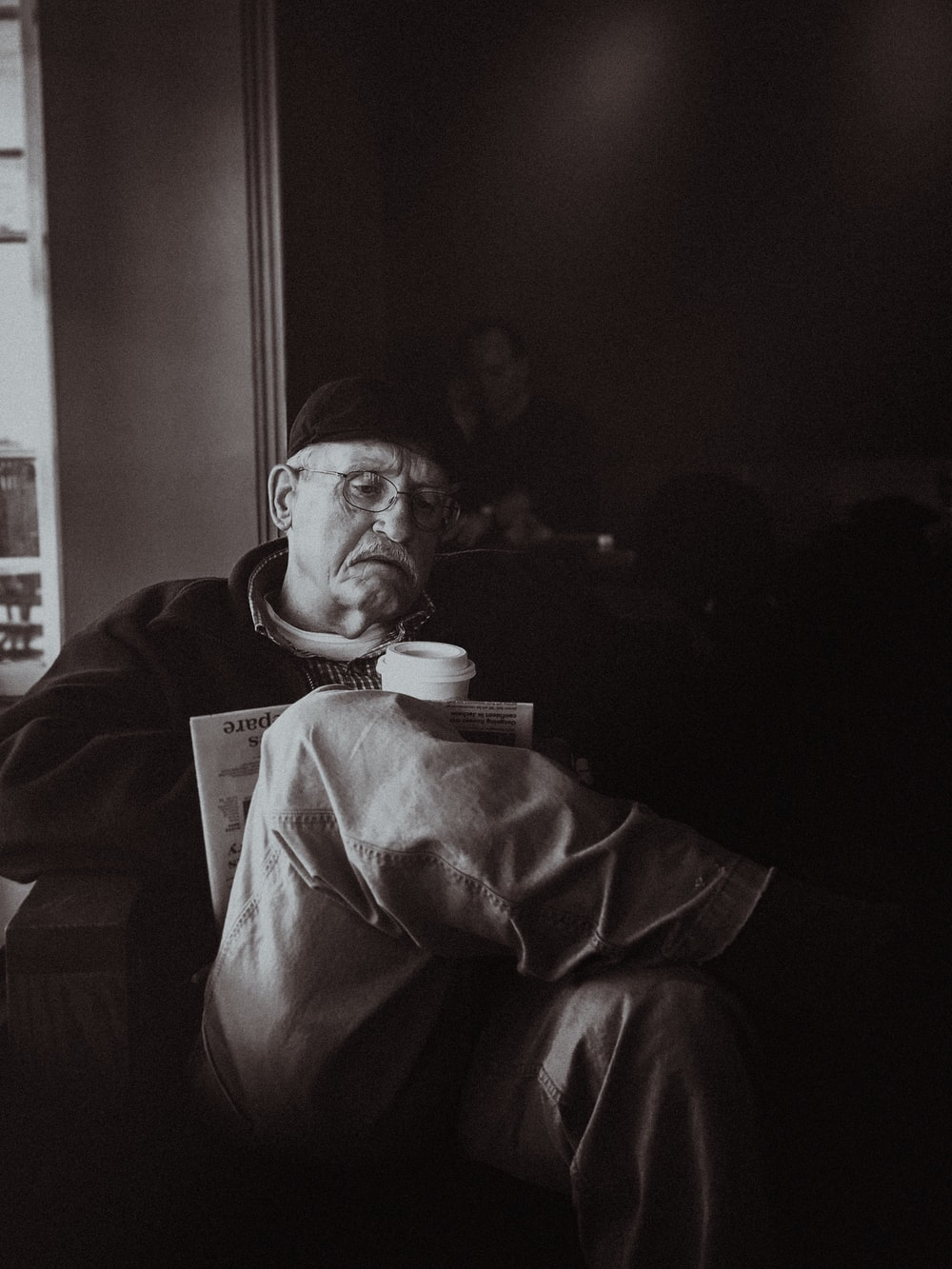 grayscale photography of man sitting on sofa chair holding coffee cup