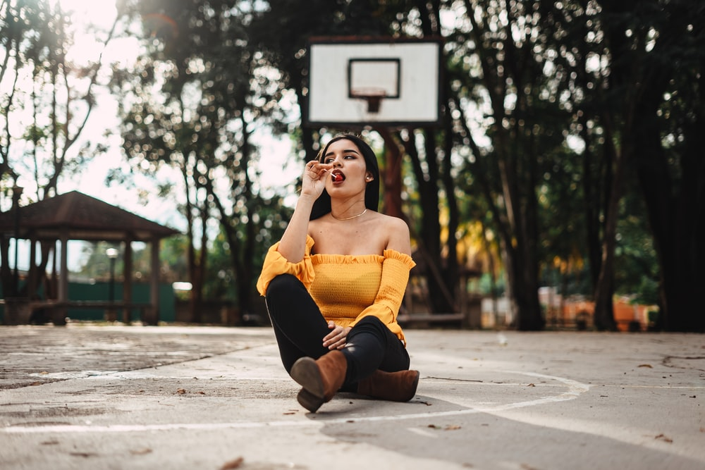 woman sitting on basketball court during daytime