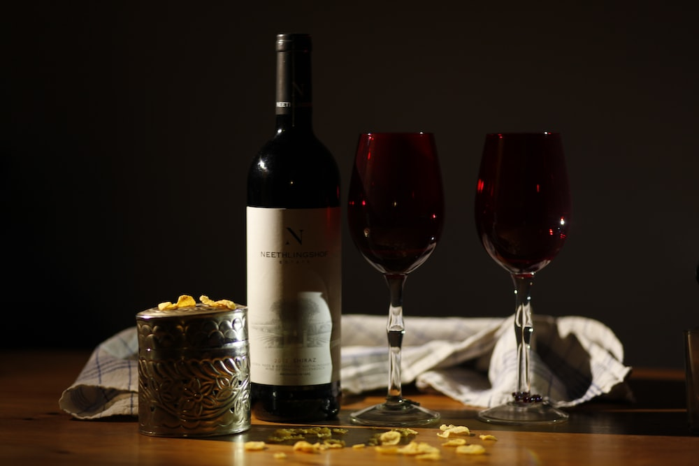 wine bottle beside two red glasses on table